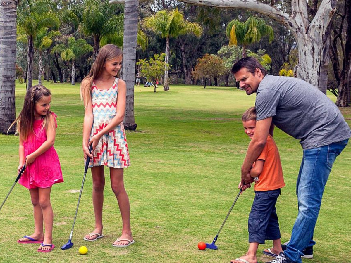 father with kids playing mini golf at oasis supa golf and adventure putt mini golf