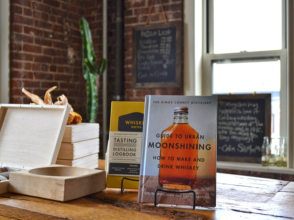 guide to urban moonshining how to make and drink whiskey book standing on wooden table