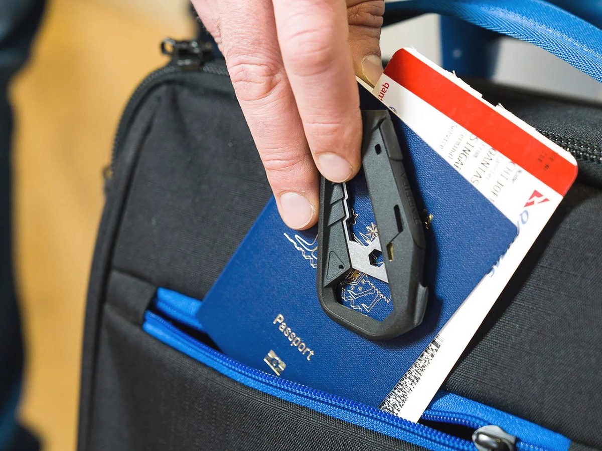 man putting tactica m 100 17 in 1 multi tool into a bag