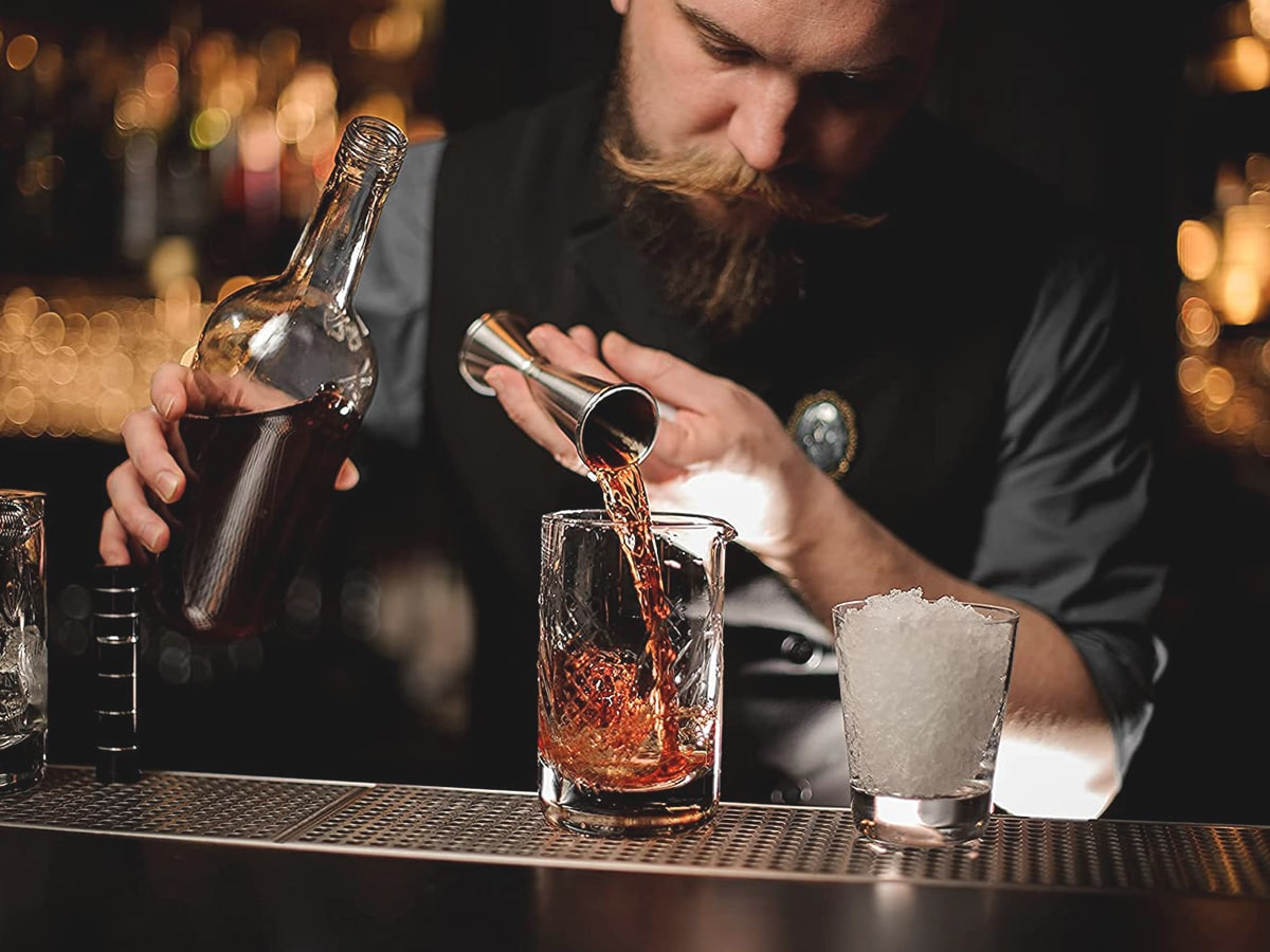barman pouring whiskey with accoutrement 11 piece cocktail kit