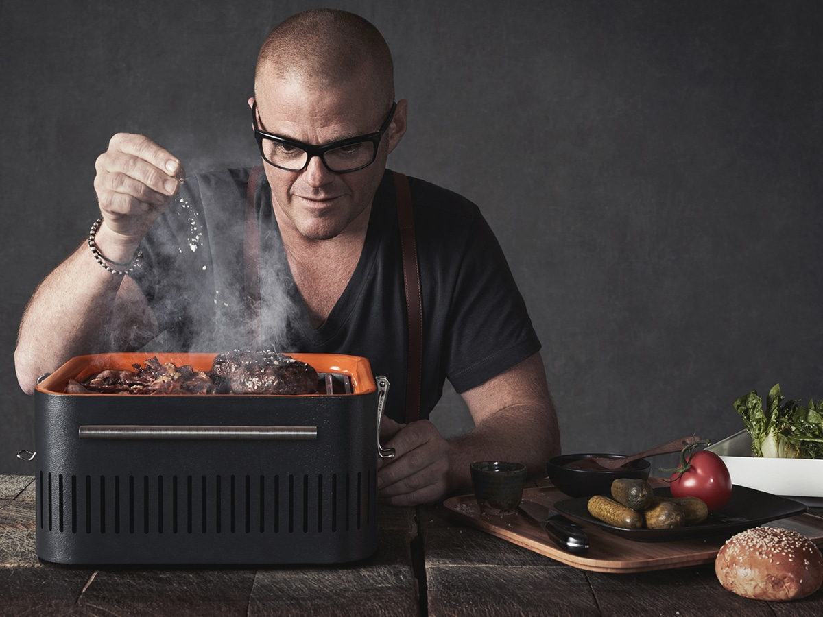 man cooking on everdure by heston blumenthal cube charcoal portable barbeque