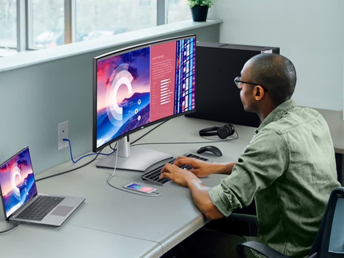 man sitting in front of Dell UltraSharp Curved Monitor