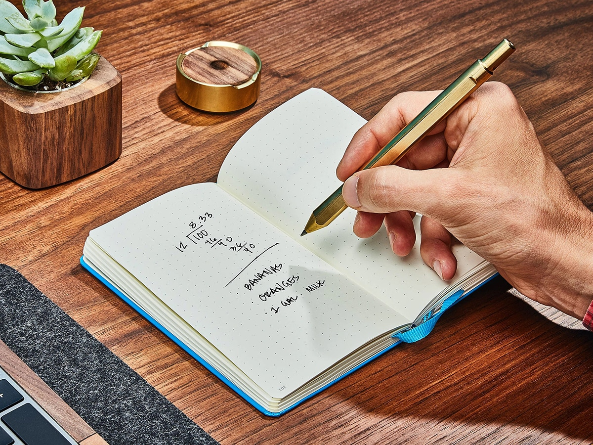 man writing in notepad with grovemade brass pen