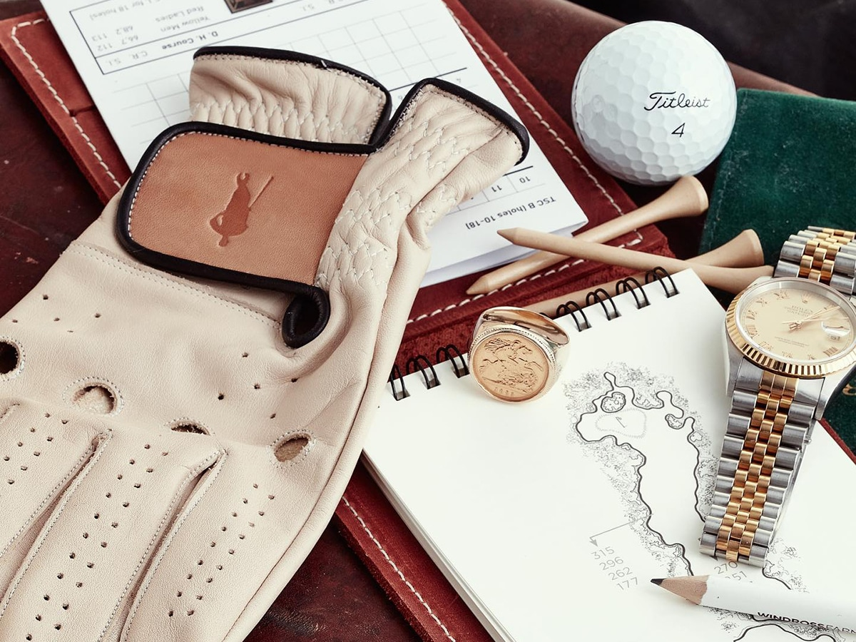 white modest vintage player leather golf gloves on notepad