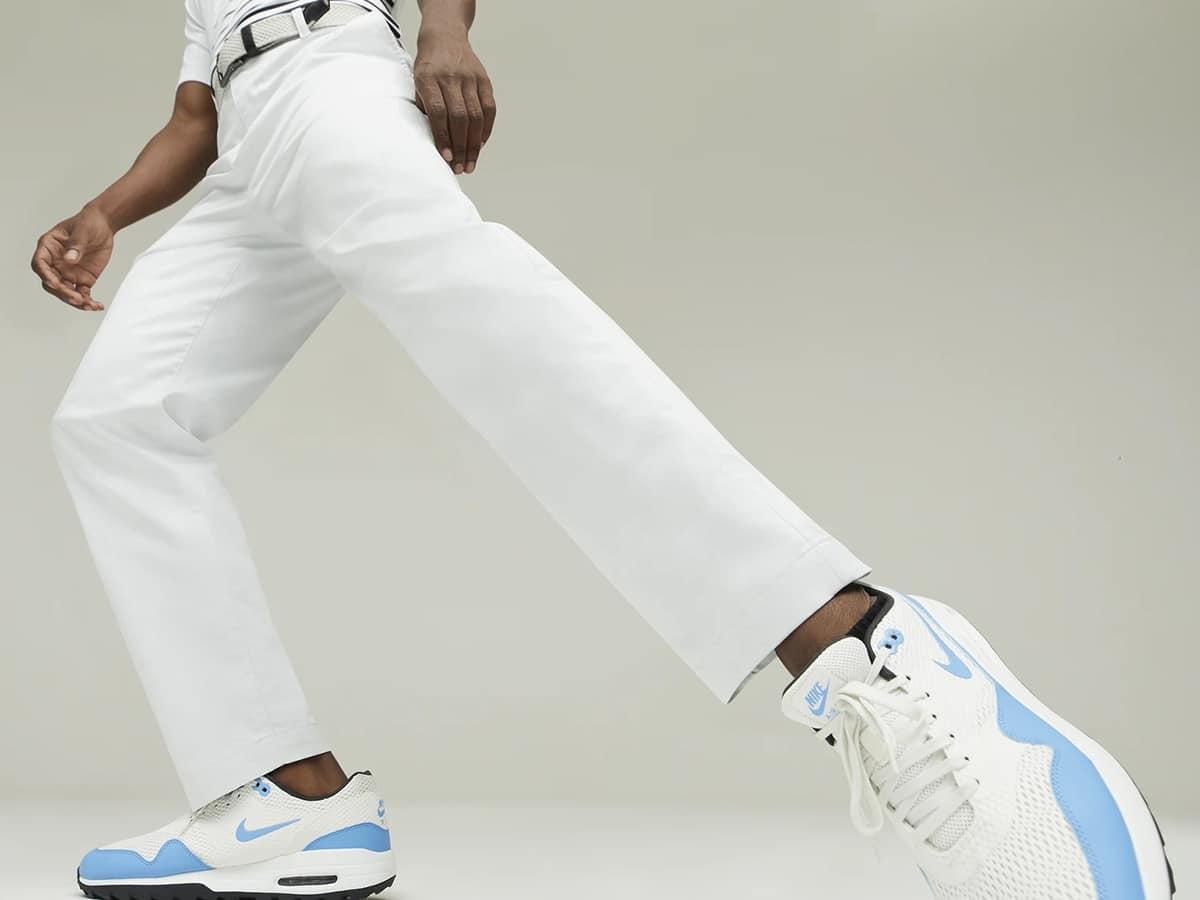 man wearing white nike dri fit uv golf chino trousers