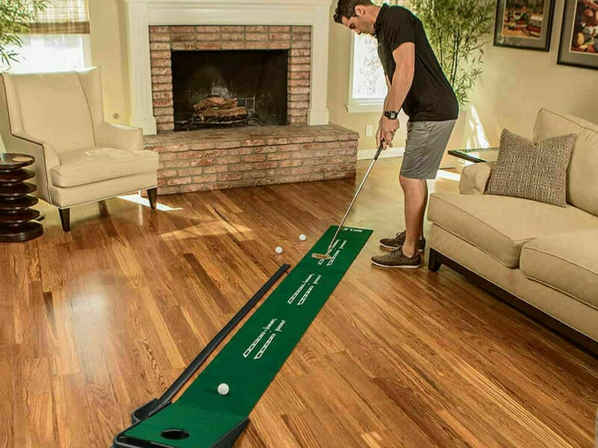 man playing mini golf sklz accelerator at home