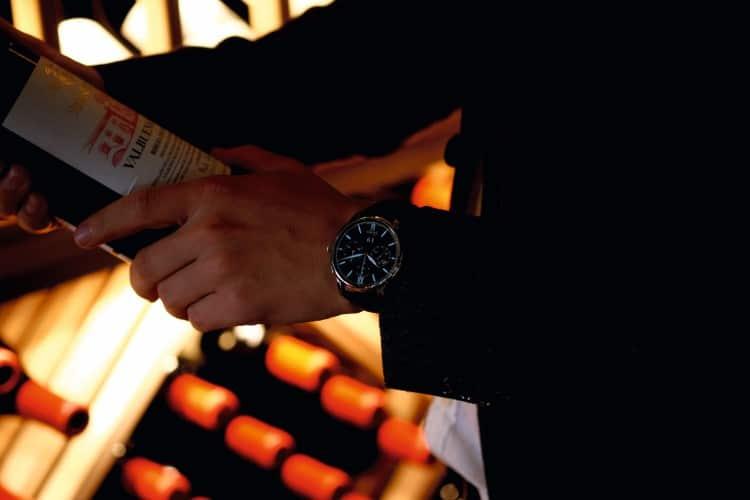 wearing glashütte original watch whiskey in hand