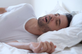 A man sleeping in bed with his mouth open