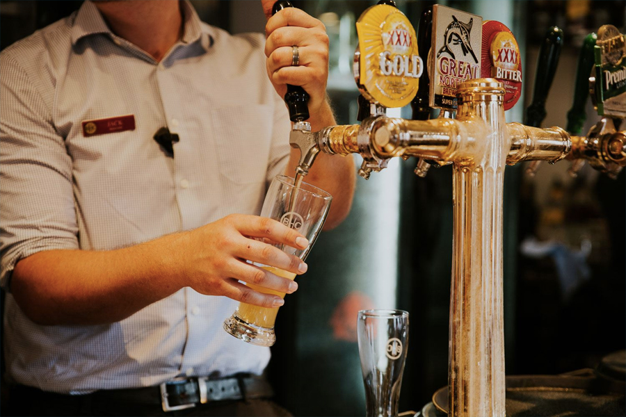 Bartender filling a glass from tap